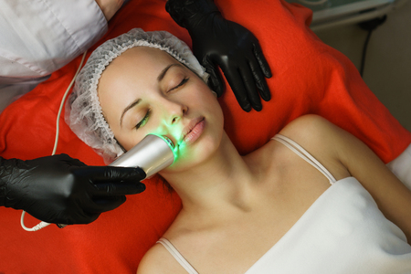Hardware cosmetology. Beautician makes ultrasonic skin tightening client. Skin pore cleansing. Anti-aging treatments. Spa. Upper lip area Stock Photo