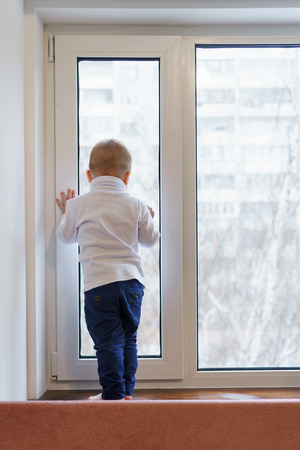 Little boy stands on windowsill and looks out window. Child is unrecognizable. Lonely childhood. Waiting for parents. Stock Photo