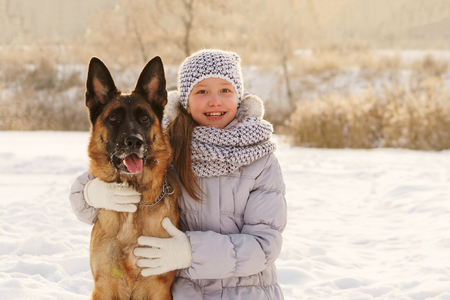 Cute girl and German shepherd for walk. Sunny winter day. Girl hugging big pet and smiling Stock Photo