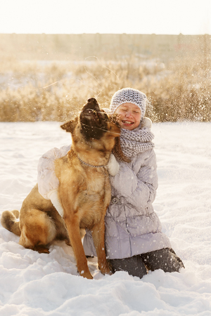 Cute girl and German shepherd for walk. Sunny winter day. Girl hugs big pet and smiles. Dog shakes his head