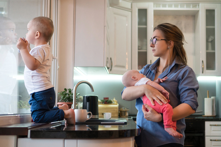 Young mother holds little daughter. Eldest son is barefoot on table and looks out window in kitchen. Family time.