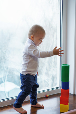 Little boy is standing barefoot on windowsill. He builds tower of cubes. Winter day outside window. Imagens