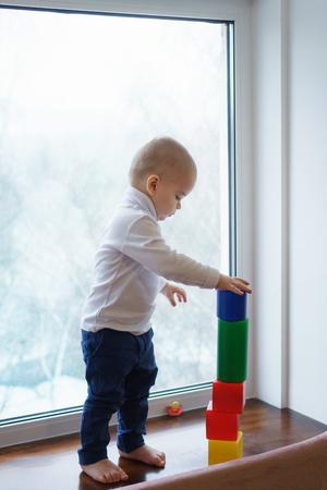 Little boy is standing barefoot on windowsill. He builds tower of blocks. Winter day outside the window.