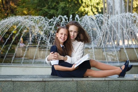 Two cute teenage sisters together read book while sitting at fountain in city park. Older girl hugs younger. Leisure time. Rest after school.