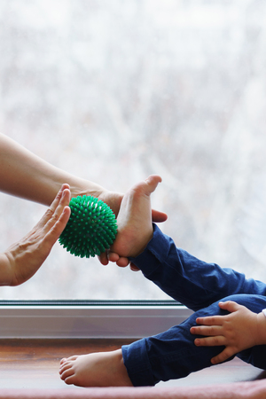 Mother does foot massage to kid. Woman holds massage ball in her hand. Child sits on windowsill barefoot. People are unrecognizable. Disease prevention Archivio Fotografico