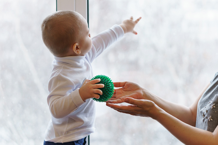 Boy holds massage ball in his hands and stands at window. Mother takes ball. Archivio Fotografico
