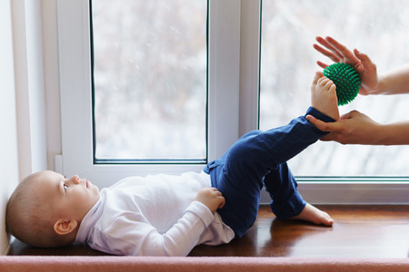 Mother makes baby massage feet. Woman holding massage ball in hand. Child lies on windowsill. Prevention of flatfoot disease