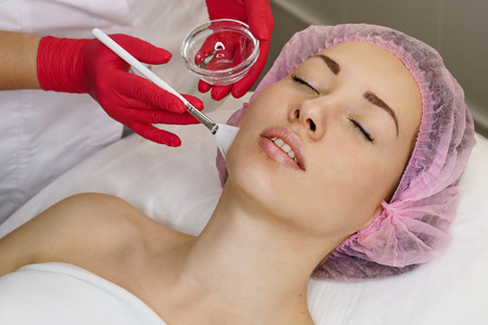 Cosmetologist applies moisturizing conductive gel before ultrasound face cleaning procedure. Spa. Cleansing skin.