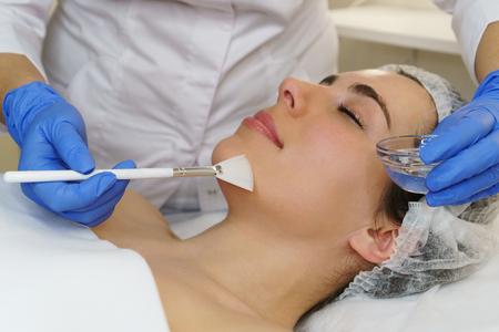 Il cosmetologo applica un gel conduttivo idratante prima della procedura di pulizia del viso ad ultrasuoni. Stazione termale. Pulizia dei pori della pelle e idratazione profonda.