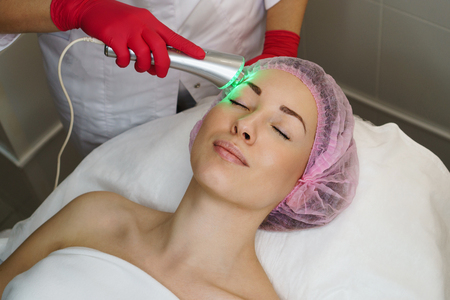 Ultrasound chromotherapy. Hardware cosmetology. Beautician carries out procedure for tightening skin of face. Spa. Non-surgical cosmetology. Skin rejuvenation Stock Photo