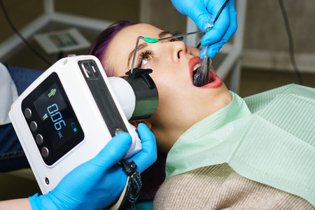 Dentist checks thickness of tooth enamel using portable x-ray. Young girl with open mouth. White teeth. Dentist hands closeup. Dental clinic.