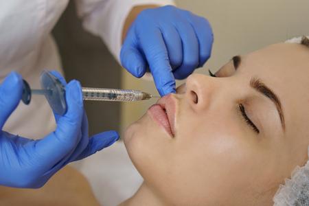 Ästhetische Kosmetik. Lippenvergrößerung im Spa-Salon. Kosmetikerin macht Injektionen Mädchen in Oberlippe. Hebeverfahren. Nahaufnahmen