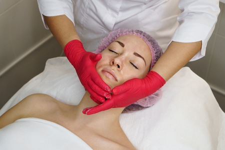 Hands of beautician make face massage girl. Regenerative therapy in spa salon. Banque d'images