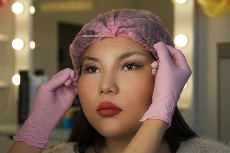 Microbleeding and eyebrow architecture. beautician builds lines of symmetry eyebrows on girl's face. Cosmetic procedure in spa salon.