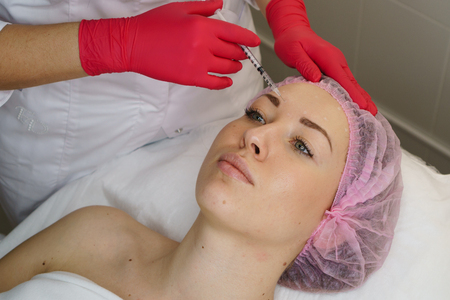 Hands cosmetologist injections in face of girl. Young woman gets beauty injections in spa salon. Medical procedures smoothing mimic wrinkles. Anti-aging injections of collagen acid Stock fotó