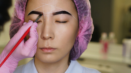 Microbleeding and eyebrow architecture. Cosmetologist applies pigment to girl's eyebrows with brush, shaping contour. Cosmetic procedure in spa salon. Face beauty.