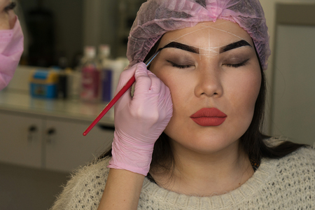 Microbleeding and eyebrow architecture. Beautician applies coloring pigment to girls brow, formation of contour. Cosmetic procedure in spa salon.