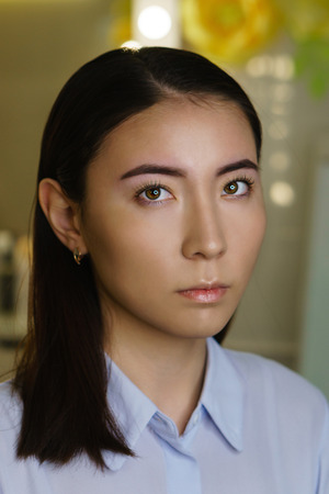 Microbleeding and eyebrow architecture. Girl after beauty procedure in spa salon. Closeup portrait