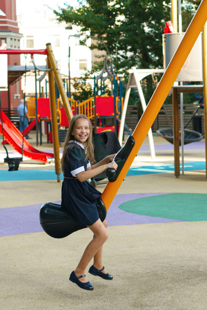 Teen girl having fun on the playground after school. Leisure. Schoolgirl riding on a swing
