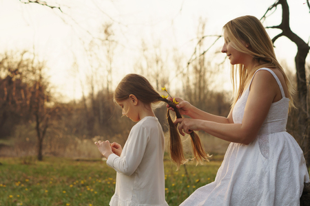 Young attractive mother braids her daughter's hair. Maternal care. Family relationships. Agreeable pastime. Family look