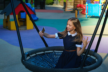 Teen girl having fun on playground after school. Leisure. Schoolgirl goes on swing and takes selfie on cell phone. Happy childhood