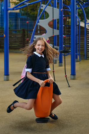 Teen girl having fun on the playground after school. Leisure. Happy childhood