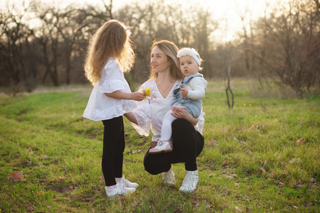 Young mother with toddler in her arms is talking with her eldest daughter on a walk. Family values. Portrait happy family on a spring meadow in rays of sunset