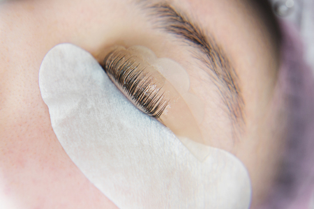 Eyelash extension procedure. Female eyes with long eyelashes. Cosmetic procedure in spa salon. Close-up of eyes and eyelashes