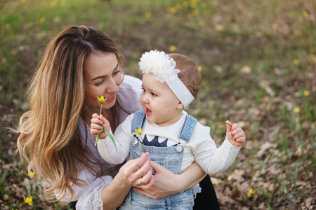 Young attractive mother shows her one-year-old daughter forest tulips. Family portrait close-up. They hold one flower in their hands, communicate and smile. Quality time. Family time Stock Photo