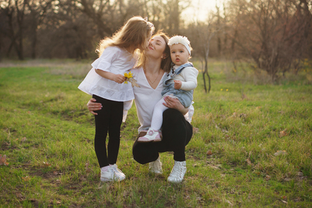 Family spring portrait. Oldest daughter kisses mom. Single mother holds toddler in her arms. Family ties concept. Mothers Day congratulation