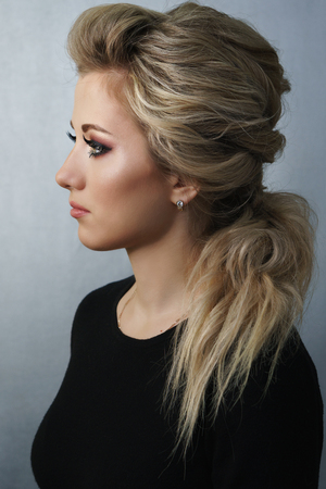 Young attractive blonde girl with hairstyle and make-up. Portrait after visiting beauty salon.