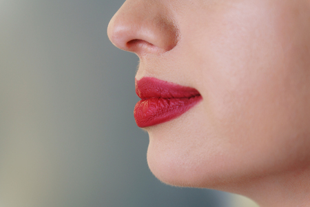 Work makeup artist. Female lips with red lipstick close-up side view. Imagens
