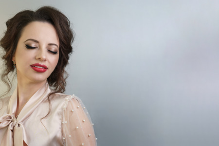 Young attractive brunette girl with hairstyle, makeup with red lipstick. Portrait after visiting beauty salon.