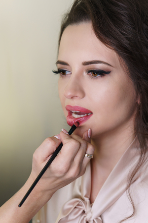 Makeup artist working in makeup studio, applies red lipstick to lips with brush. Close-up of a woman's face.