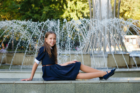 Attractive European girl in school uniform posing in front of a fountain in a city park. Leisure time