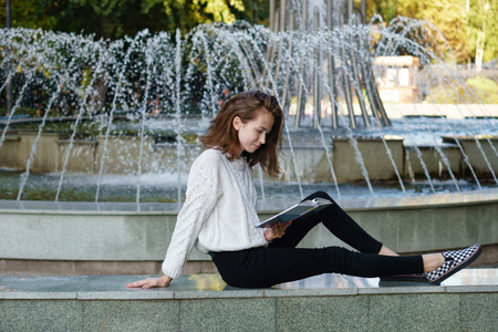 Attractive student in casual style is sitting by fountain reading a book. Self-education in free time, bachelor campus life rhythm. Standard-Bild