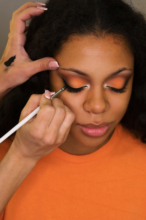 Makeup artist draws arrows on eyelids of african american girl. Evening make-up. Closeup portrait