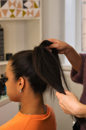 Hands professional female hairdresser doing evening hairstyle for her client. Hairdressing services. Ð¡reating hairstyle. Hair styling process. Beauty industry. Stock Photo