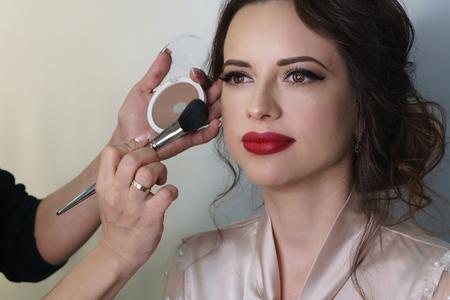 Maquilleuse travaillant dans un studio de maquillage, applique un pinceau de maquillage sur le visage. Visage de femme se bouchent. Banque d'images