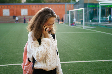 Young girl in a white sweater tries to call. High school student holding a mobile device. Phone call on school grounds. Soccer field in background