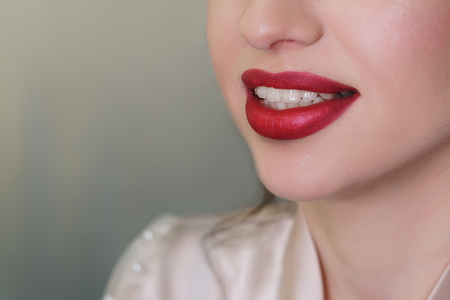 Work makeup artist. Female lips with red lipstick closeup. The girl smiles.