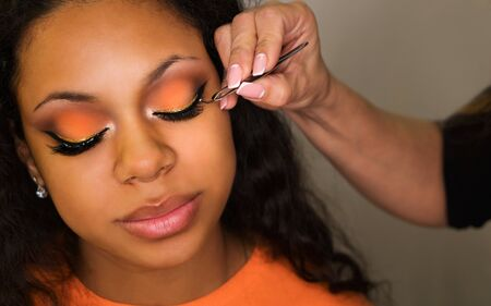 Makeup artist sticks false eyelashes of african american girl. Evening make-up. Closeup portrait.