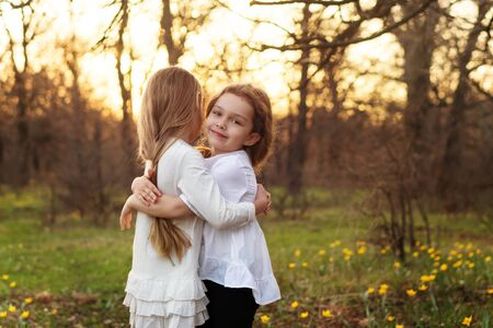 Best friends happy to meet you. Girls in white dresses cuddling in spring meadow. Family bonds Archivio Fotografico