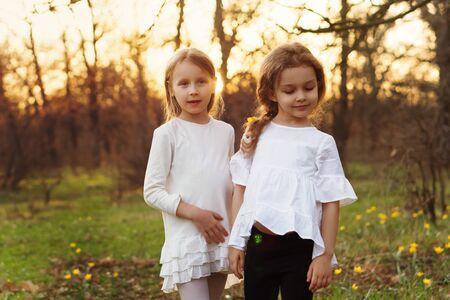 Stijlvol portret van zussen in de lenteweide. Meisjes poseren in witte jurken. Familie foto