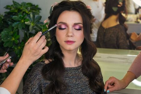 �¡reating creative image for photoshoot. Makeup artist corrects make-up on model, hairstyle master pat hair back into place. Delicate and fun customer service. Beauty industry