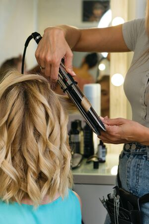 Hairtician twirls curls with flat iron hair. Back view. Hairdressing services. Creation of evening hairstyles fashionable stylish women's hairstyles. Hair styling process. Courses in hairdressing. Beauty service concept.