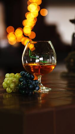 French grape brandy, strong alcoholic drink. Still life. Glass of cognac and bunch of grapes. Service and tasting concept. Stok Fotoğraf