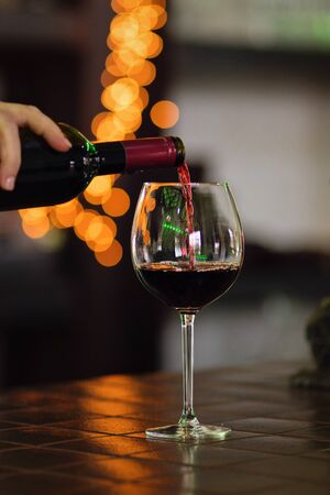 Red wine pouring into wine glass. Shallow depth of field. Bokeh. Warm toning. Space for text. Concept alcoholic drinks.