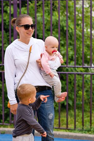 Small childrenspend time with mom. Young mother walks with children. Happy family. Young mommy fooling around with a child. Good relations of parent and child. Happy moments together.