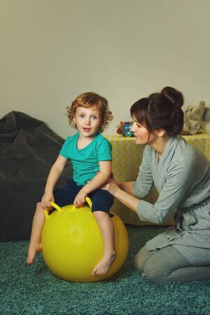 Stylish mother with a charming little son spend time in the childrens room. Morning work-out. Boy on fitball. Healthy lifestyle. Good habits from childhood Stock Photo